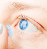 Close up of inserting a contact lens in female eye — Stockfoto
