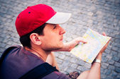 Tourists on the street looking at a guide — Stock Photo