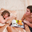 Happy man and woman having luxury hotel breakfast in bed togethe — Stok fotoğraf