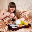 Woman eating breakfast and drinking coffee in bed. Young woman s — Stok fotoğraf
