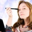 Stock Photo: Pretty womapplying make up.