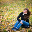 Stock Photo: Young woman sits on leaves in autumn park