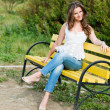 Beautiful woman sit on a bench in park  — Stock Photo