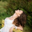 Beautiful woman relax on the bench in park — Stock Photo #21576589