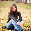 Young woman sits on leaves in autumn park — Stock Photo #21577163