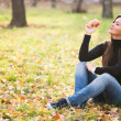 Portrait of beautiful young woman with apple in autumn park — Stock Photo