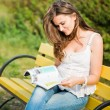 Woman read a magazine in park — Stock Photo #21577431