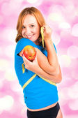 Portrait of a young sport woman holding apple and measuring tape — Stock Photo