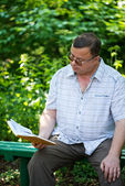 Relaxed casual man sitting in park and reading — Foto Stock