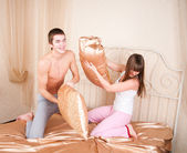 Happy young couple having fun on the bed — Stock Photo
