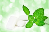 Chewing gym and fresh leaves of mint — Stock Photo