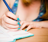 Hand of young woman taking notes — Stock Photo
