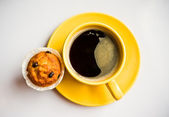 Coffee in an yellow cup and a muffin — Stock Photo