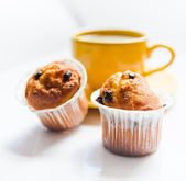 Coffee in an yellow cup and muffins — Stock Photo