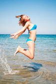 Young girl jumping out of a water — Stock Photo