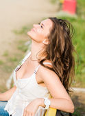 Beautiful woman relax on the bench in park — Stock Photo