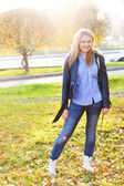 Portrait of beautiful young woman walking outdoors in autumn — Stock Photo