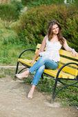 Linda mulher sentar em um banco no parque — Fotografia Stock
