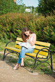 Woman read a magazin in park — Stock Photo