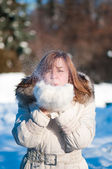 Mooie vrouw waait in de sneeuw — Stockfoto