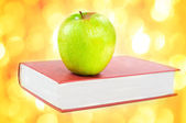 A green apple on a book — Stock Photo