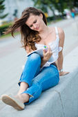 Outdoor portrait of young woman with fashion magazine — Stock Photo