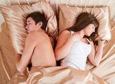 Couple bouleversé dormir séparément sur leur lit — Photo