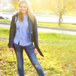 Stock Photo: Portrait of beautiful young woman walking outdoors in autumn