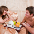 Happy man and woman having luxury hotel breakfast in bed together — Stock fotografie