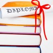 Diploma with red ribbon and books — Foto de Stock