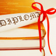 Diploma with red ribbon and books — Stock Photo