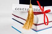 Graduation cap with book and diploma — Stock Photo