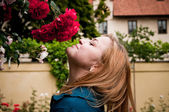 Pretty young woman smelling a rose — Stock Photo