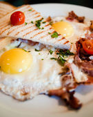 Fried eggs with bacon and toasts — Stock Photo