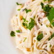 Spaghetti . Fettuccine carbonara in a white bowl, garnished with bacon, mushrooms and parsley — Stock Photo