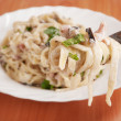 Spaghetti . Fettuccine carbonara in a white bowl, garnished with bacon, mushrooms and parsley. — Stock Photo #22851242