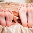 Stock Photo: Bared heels of pair in stick out from under bed-sheets