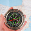 Compass in the hand,map in the background — Stok fotoğraf