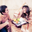 Happy man and woman having luxury hotel breakfast in bed togethe - Stock Photo