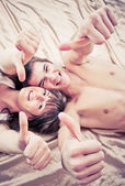 Happy couple lying on bed with thumbs up — Stock Photo
