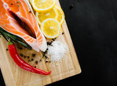 Salmon and spices on a wooden board — Stock Photo