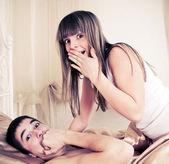 Zaskoczony sex para leży w łóżku — Zdjęcie stockowe