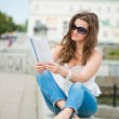 Outdoor portrait of young woman with fashion magazine — Stock Photo #24594533