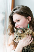 Beautiful smiling brunette girl and her cat over — 图库照片