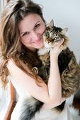 красивая улыбается девушка брюнетка и ее кот над — Стоковое фото