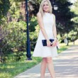 Beautiful young blond woman in a white dress outdoors — Stock Photo