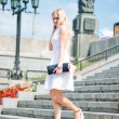 Beautiful  blond woman  walking down stairs outdoors — Stock Photo