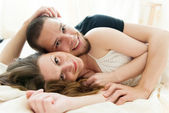Lovely couple hugging on their bed at home — Stockfoto