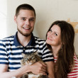 Happy young couple at home with their cat — Stock Photo
