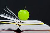 Pila di libri con mela verde e pulito lavagna — Foto Stock